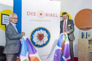 Heinrisch Riethmüller und Christoph Rösel enthüllen die große Lutherbibel. Foto: DBG