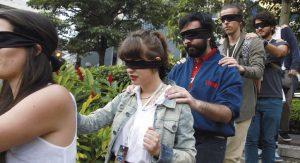 Bei einer Stadtführungs-Aktion der Bibelgesellschaft in Costa Rica gehen alle mit verbundenen Augen hintereinander. Jeder legt seine Hand auf die Schulter des Vorangehenden, um nicht zu stolpern. So machen es blinde Menschen, wenn sie keinen Blindenstock haben. Foto: UBS